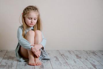 Sad girl sitting alone on the floor