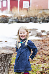 Portrait of young blonde smiling girl standing in backyard