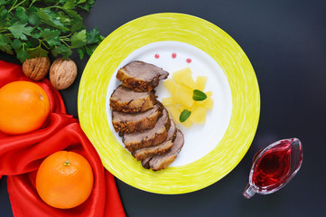 Duck breast Magret with pieces of pineapple on a ceramic plate on a black background. French traditional meat dish. Christmas menu. Festive kitchen.