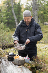 Man cooking meat while camping