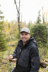 Smiling man standing in forest with water in wooden mug