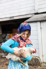 Girl in folk costume holding chicken