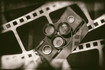 Old retro movie camera on background of perforation film