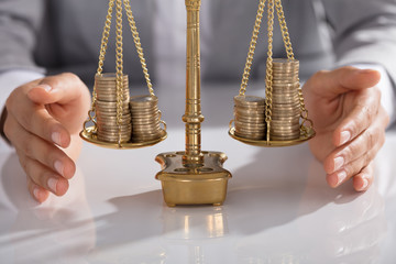 Businessperson Protecting Justice Scale With Stacked Of Coins