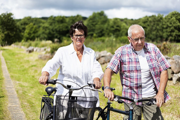 Senior couple walking with bicycles in countryside