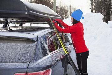 Young woman attaching rooftop cargo box to car in winter