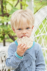 Portrait of blond baby boy eating rice corn cake