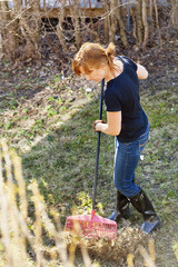Red haired woman raking grass on sunny day