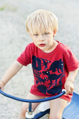 Portrait of young blond boy sitting on three wheel bicycle