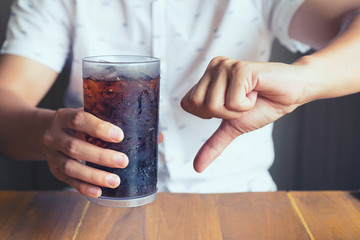 Glass of soft drink splashing with ice on hand wooden table background, not good bad for health  finger symbol