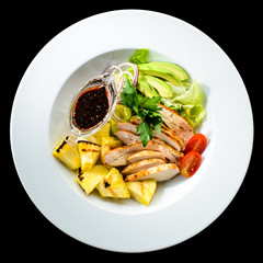 Salad with grilled chicken and pineapple in a white plate isolated on black background