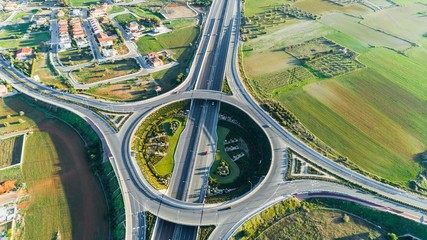 Aerial bird's eye view of GSP roundabout and A1 highway from Limassol to Nicosia city, Latsia, Cyprus. The circular intersection with cars driving, no traffic over the main motorway street from above.