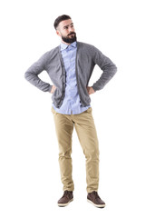 Handsome stylish bearded man thinking and looking up with arms on hips. Full body length portrait isolated on white studio background.