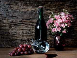 Still life visual art of grapes, a falled glass of wine, a bottle of wine and pink roses in a red vase on wooden slab with wooden back drop