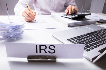 IRS Nameplate In Front Of Accountant Calculating Tax