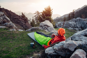 Male hiker rest, drinks coffee and enjoying misty landscape
