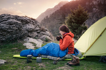 Female traveler in sleeping bag near the tent in mountains, Turkey