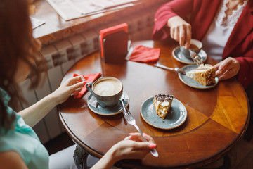 Two women chatting in a coffee shop, cake on the table