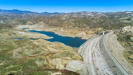 Aerial bird eye view of Kalavasos rockfill dam, Larnaca, Cyprus. The street bridge over the reservoir crossing Vasilikos river and the hills around the water from above.
