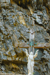 Jesus Christ statue in the rock with hands pointing to the sky