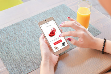 Woman buy red shoes online . Mobile app or web site on screen. Table and juice in background.