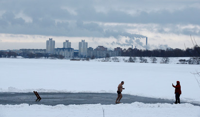 Man runs after diving in icy waters of a lake during Orthodox Epiphany celebrations in Minsk