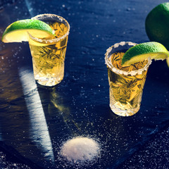 Gold Mexican tequila with lime and salt on dark table, toned image