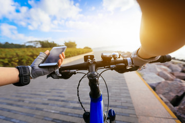 Cyclist using smartphone for navigation when riding mountain bike on the sunrise coast