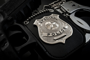 Protect and serve, crime fighting and blue lives matter concept with a police badge, a gun and a pair of handcuffs at night