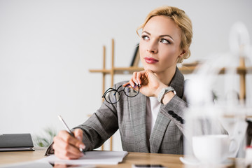 portrait of pensive businesswoman looking away at workplace