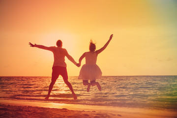 Happy loving couple enjoy tropical beach vacation at sunset