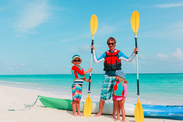 father with little son and daugther kayaking at beach