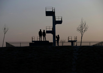 Boys take a picture with a mobile phone on the top of a hill beside an empty swimming pool early in the morning in Kabul