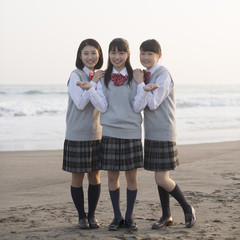 砂浜で微笑む女子校生