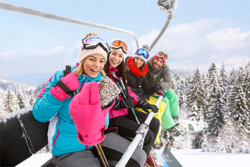 Girls with guy in ski lift taking photo