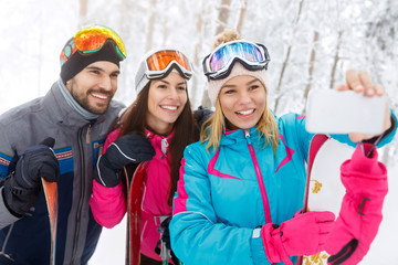 Woman with friends taking selfie on skiing