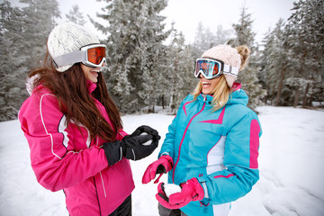 Two girls making snowball on skiing