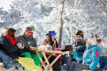 Skiers group refreshing with drink after skiing