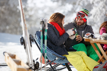 Male skier toasting with female skier