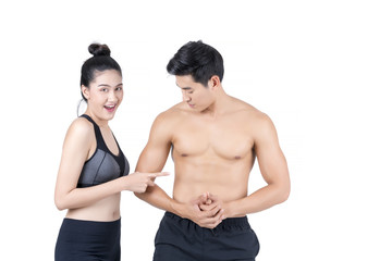 Young Asian woman in sportswear pointing at six-pack of handsome muscular young Asian man isolated on white background