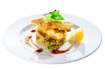 Delicious fried cod fillet with risotto, salad and lemon in a white plate isolated on white background