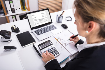 Businesswoman Calculating Invoice Using Calculator And Laptop