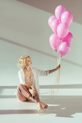 beautiful young woman in pink bra holding pink balloons while sitting on grey