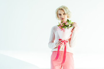 beautiful blonde woman in pink clothes holding bouquet of flowers and looking at camera isolated on white