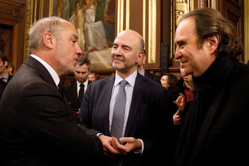 Head of French telecom company Orange Richard speaks with European Economic and Financial Affairs Commissioner Pierre Moscovici and French telecom Iliad Group founder Xavier Niel in Paris
