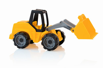 Yellow excavator isolated on white background with shadow reflection. Plastic child toy on white backdrop. Construction vehicle. Children's toy. Tractor Toy.