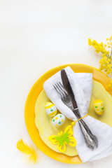 Easter table setting with yellow plates and vintage silverware wrapped in white napkin with traditional Easter decorations on white wooden background. With plenty of copy space for your greeting text