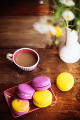 A cup of hot black coffee and bright macaroons on a wooden table at dark background with colorful bokeh