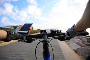 Cyclist using smartphone for navigation when riding mountain bike on the coast path