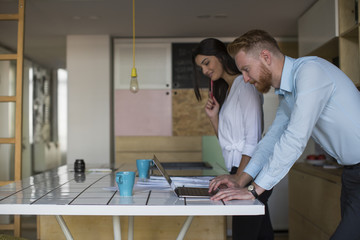 Smiling man with woman using laptop on table at home